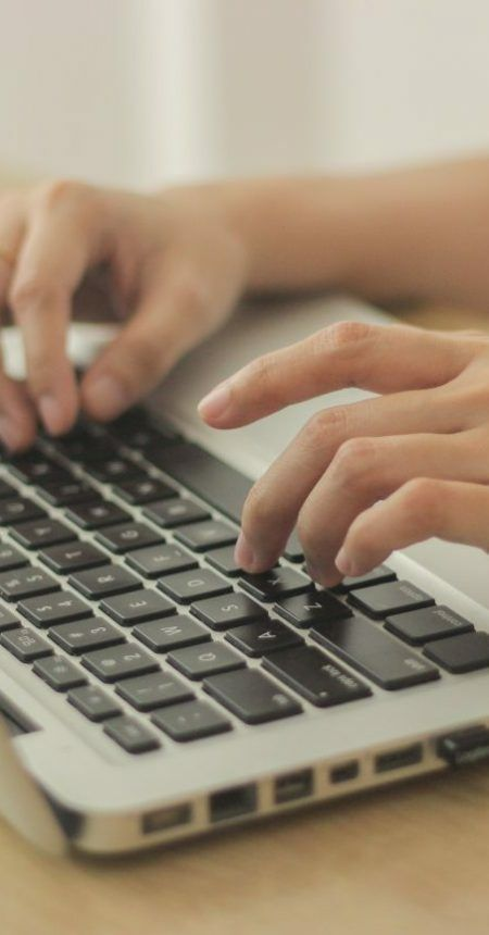 person-sitting-in-front-of-desk-and-typing-on-the-keyboard-of-the-laptop